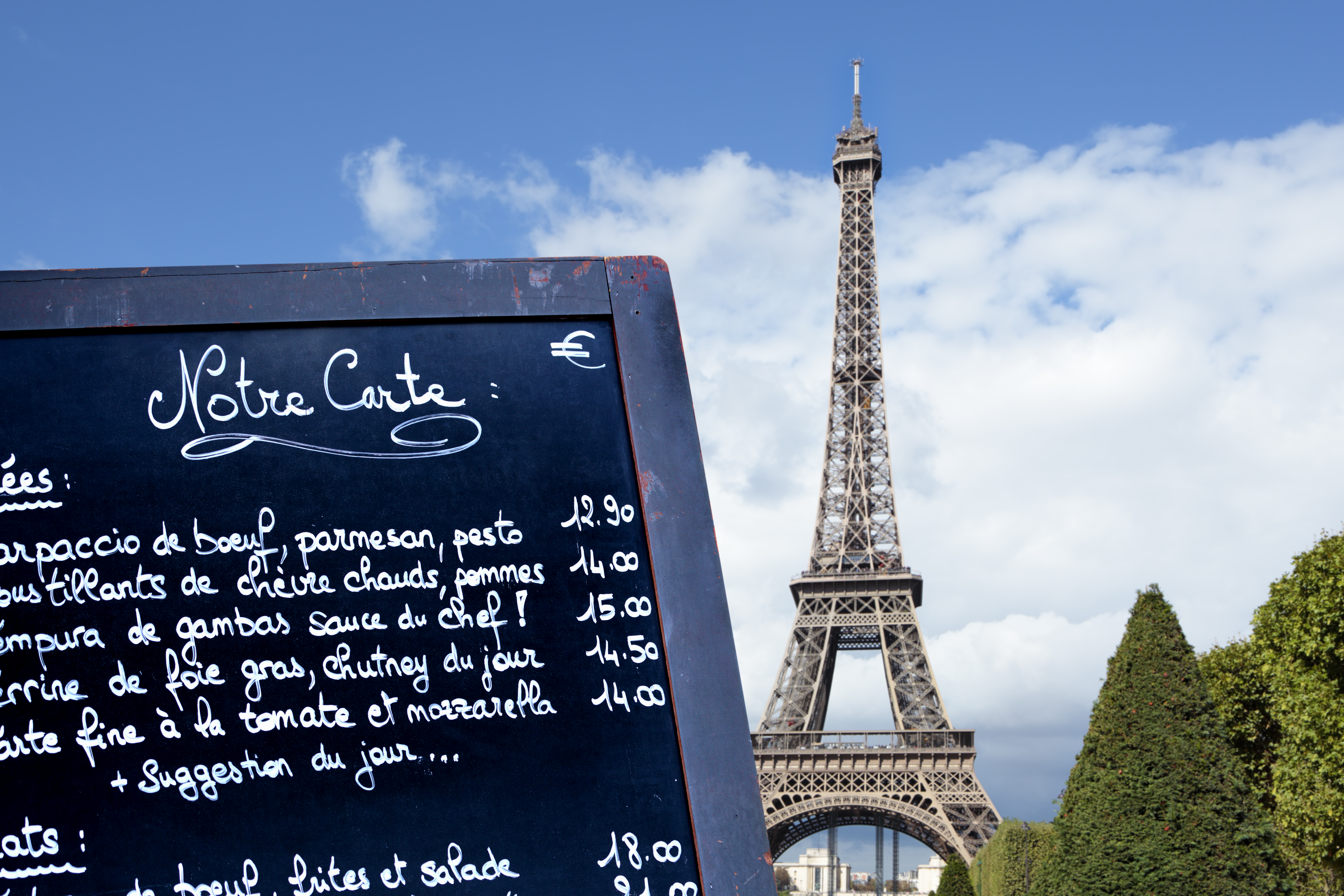 Typical Paris restaurant menu board with Eiffel Tower in the distance.